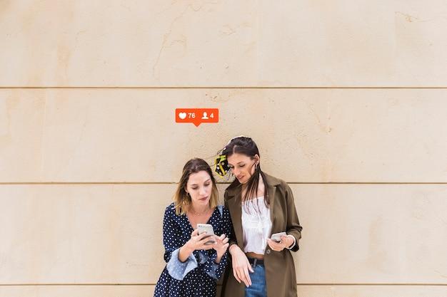 Zwei freundinnen, die likes betrachten und mitteilungmitteilung auf mobiltelefon