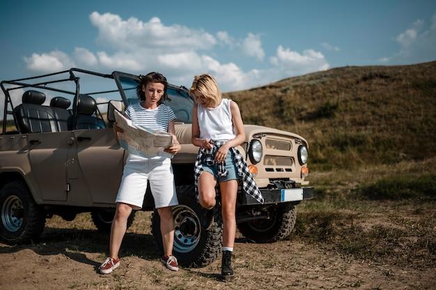 Zwei freundinnen, die mit dem auto reisen und karte überprüfen