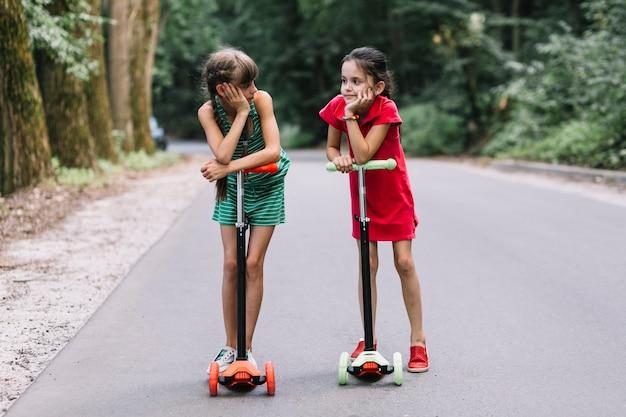 Zwei freundinnen, die mit stoßroller auf straße stehen
