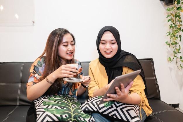 Zwei freundinnen, die tablette benutzen und einen kaffee im café trinken