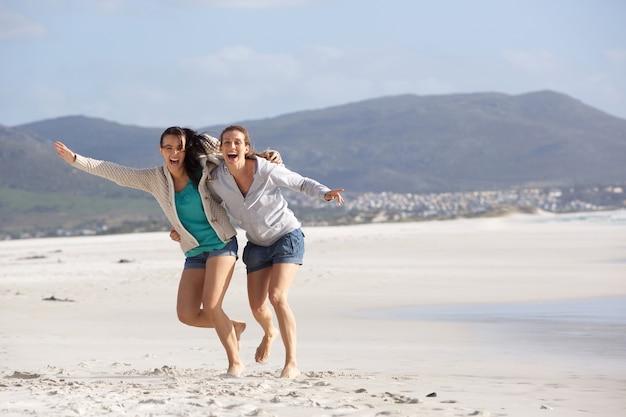 Zwei freundinnen, die über den strand lachen