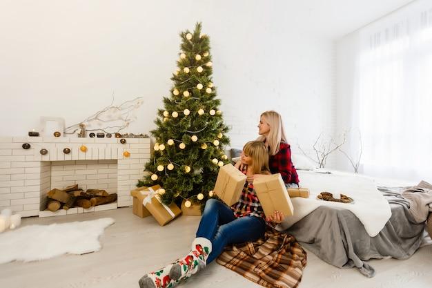 Zwei freundinnen, die weihnachtsgeschenke austauschen