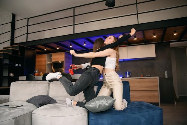 Zwei freundinnen, die zu hause mit aufregungsvideospielen spielen, während sie sich ausruhen und den urlaub genießen