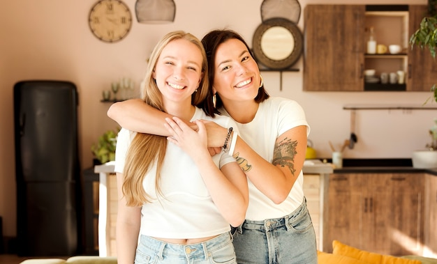 Zwei freundinnen, die zu hause umarmen. entzückendes lesbisches paar. beste freunde, liebevoll und glücklich.