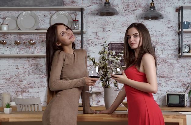 Zwei freundinnen, die zusammen wein in der küche trinken