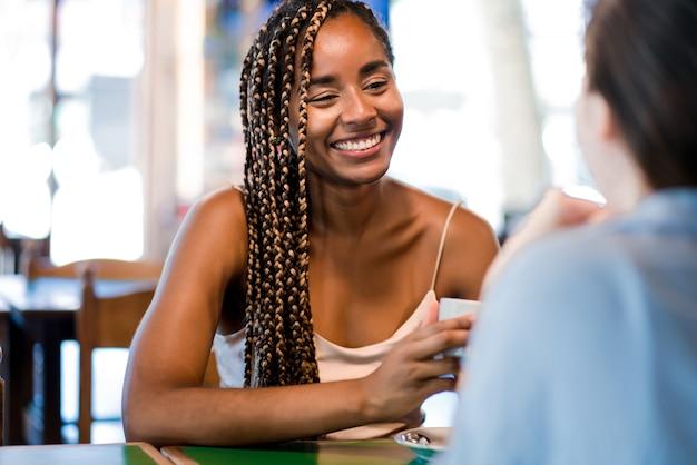 Zwei freundinnen genießen die gemeinsame zeit beim trinken einer tasse kaffee in einem café. freunde-konzept.