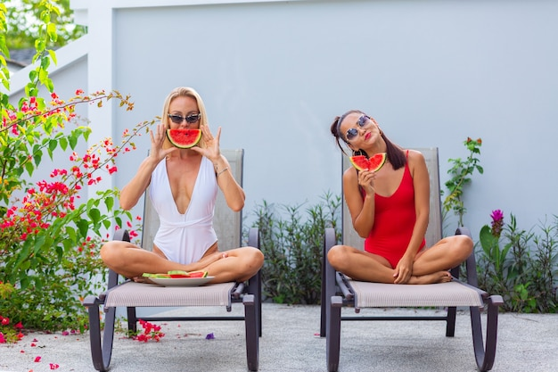Zwei freundinnen im badeanzug asiatisch und kaukasisch auf sonnenliege durch pool bei villa mit wassermelonenferien in tropischen ländern frische früchte