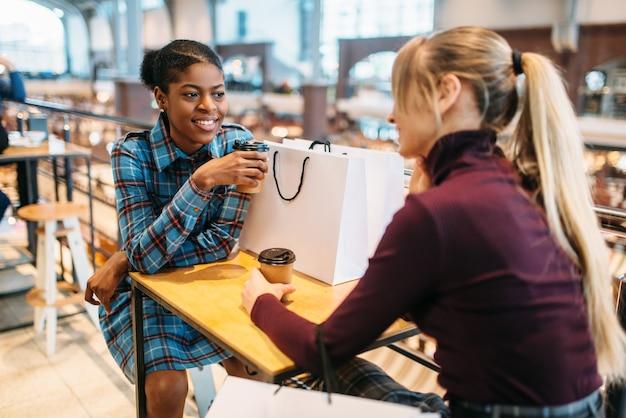 Zwei freundinnen im food-court nach dem einkauf