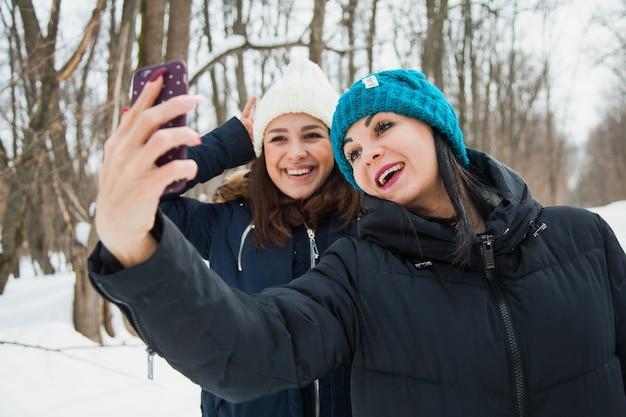 Zwei freundinnen im freien in strickmützen an einem schneekalten winterwetter. lächelnde mädchen in warmen kleidern machen selfie auf schnee
