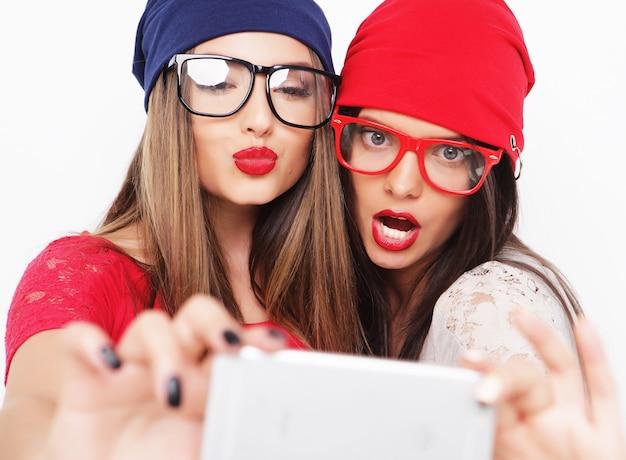 Zwei freundinnen im teenageralter im hipster-outfit machen selfie auf einem telefon.