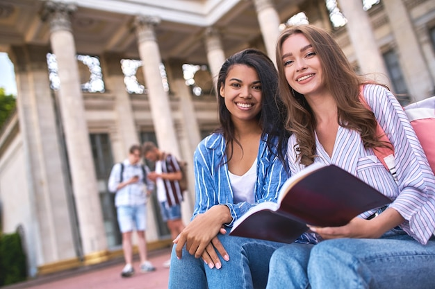 Zwei freundinnen im vordergrund im fokus sitzen auf den stufen und schauen in die kamera