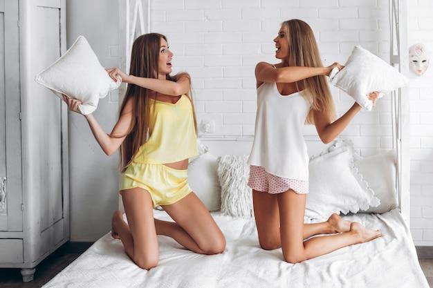 Zwei freundinnen in der unterwäsche, die kissenschlacht im schlafzimmer hat