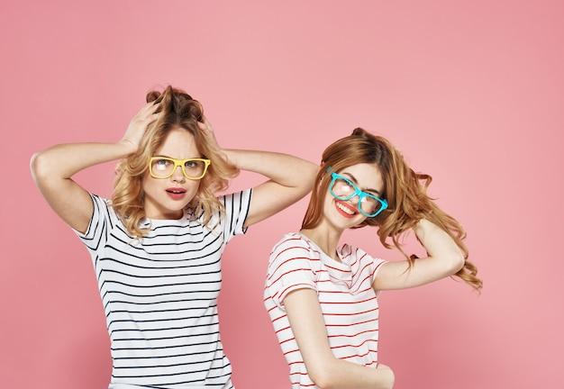Zwei freundinnen in gestreiften t-shirts, die brille mode spaß lebensstil isolierte wand tragen.