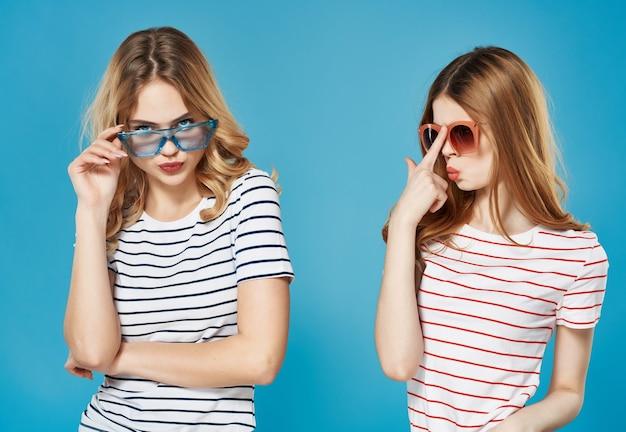 Zwei freundinnen in gestreiften t-shirts modische brillenunterhaltungs-glamour-blauer hintergrund