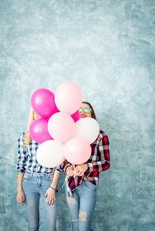 Zwei freundinnen in karierten hemden, die sich mit luftballons auf dem blauen wandhintergrund amüsieren