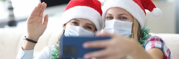 Zwei freundinnen in schützenden gesichtsmasken und roten weihnachtsmützen werden auf telefonporträt fotografiert