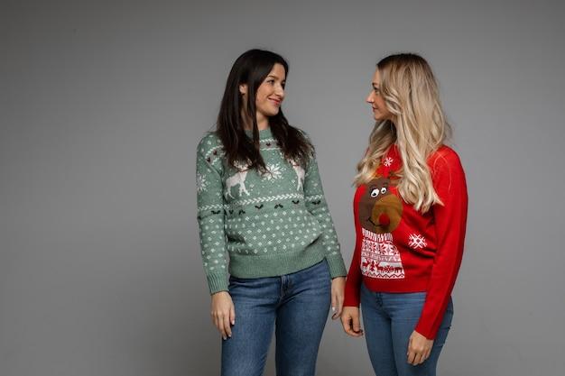 Zwei freundinnen in warmen pullovern lächeln zusammen
