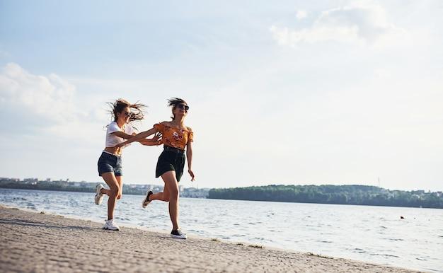 Zwei freundinnen laufen und haben spaß am strand in der nähe des sees bei sonnigem tag.