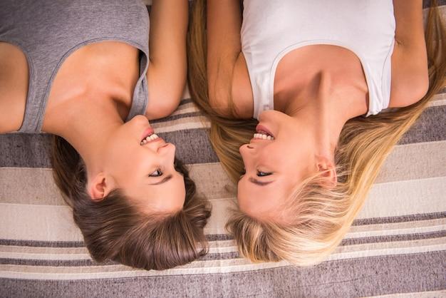 Zwei freundinnen liegen auf dem bett und lachen.