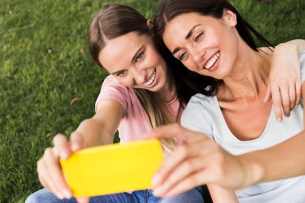 Zwei freundinnen machen ein selfie im freien