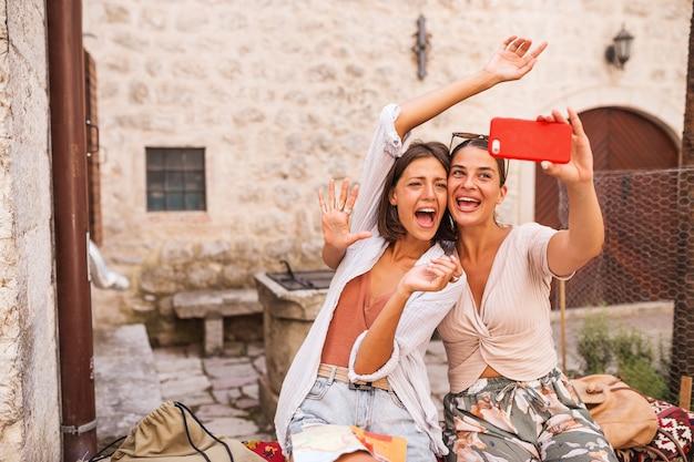 Zwei freundinnen machen selfie in der stadt