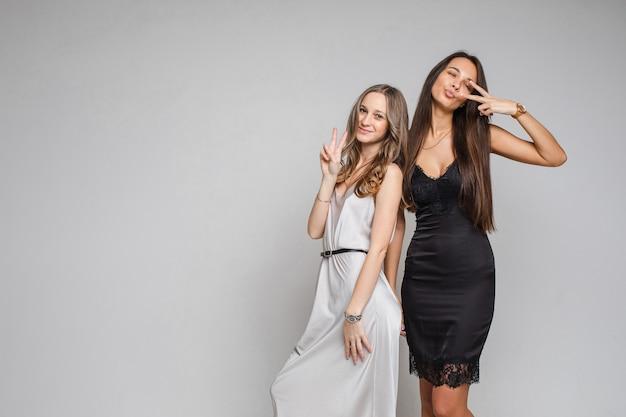 Zwei freundinnen mit braunen haaren in schönen schwarzen und weißen kleidern feiern das neue jahr mit einem lächeln