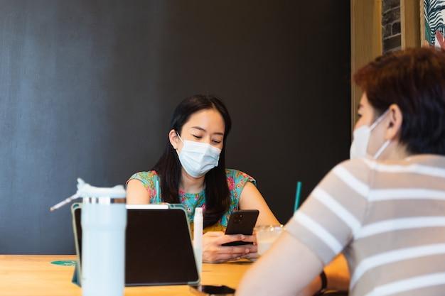 Zwei freundinnen mit einer schutzmaske, die auf einem café sitzt und handy schaut