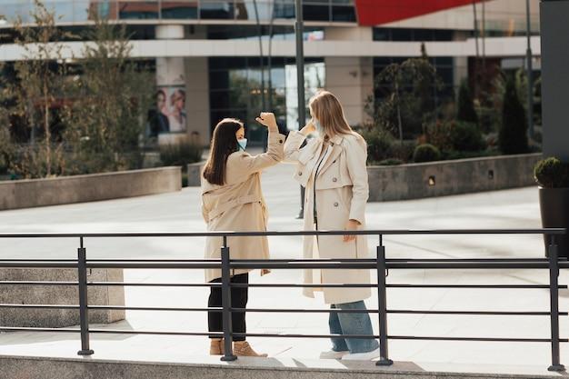 Zwei freundinnen mit schutzgesichtsmasken grüßen, indem sie ellbogen stoßen. begrüßung des ellenbogens, um die ausbreitung des coronavirus zu vermeiden.