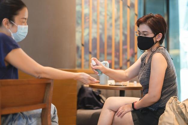Zwei freundinnen mit spray ihre hände mit antiseptischem spray im café