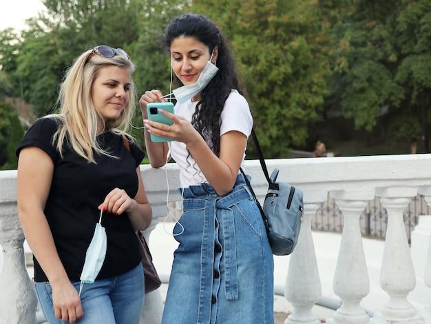 Zwei freundinnen nahmen ihre schutzmasken ab, um gemeinsam über kopfhörer musik zu hören