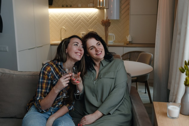 Zwei freundinnen sitzen auf der couch, heben ihre brille und schauen aus dem fenster.