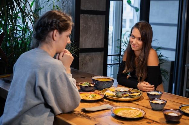 Zwei freundinnen sitzen und essen ein paar snacks in einem café