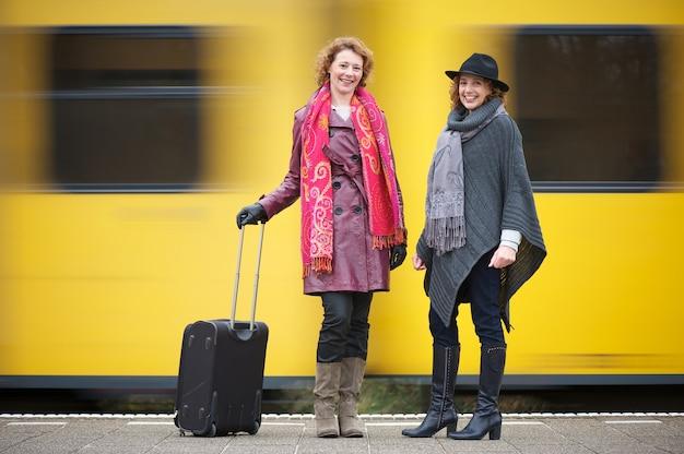 Zwei freundinnen stehen auf der bahnstationsplattform mit gepäck als gelbe zuggeschwindigkeiten