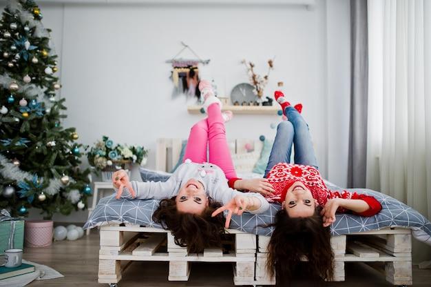 Zwei freundinnen tragen auf den winterstrickjacken, die spaß auf bett am raum mit chrismas dekorationen haben.