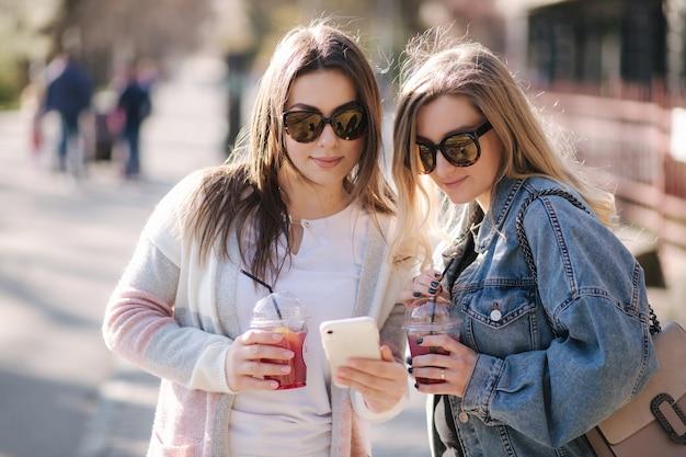 Zwei freundinnen trinken himbeerlimonade und schauen auf das telefon im freien