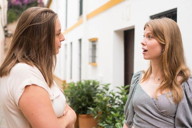 Zwei freundinnen unterhalten sich auf der straße einer europäischen stadt zwei freundinnen