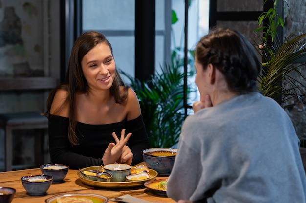 Zwei freundinnen unterhalten sich drinnen in einem asiatischen café