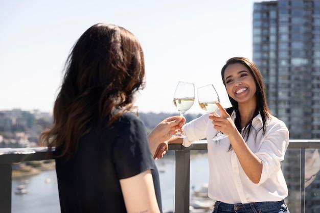 Zwei freundinnen unterhalten sich und genießen wein auf einer dachterrasse