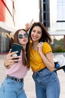 Zwei freundinnen verbringen zeit miteinander im freien und machen selfies