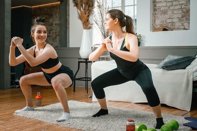 Zwei freundinnen zu hause lächeln und sport treiben