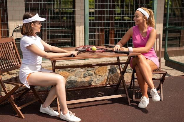 Zwei freundliche junge tennisspieler in aktivkleidung, die in der pause am tisch sitzen und sich unterhalten