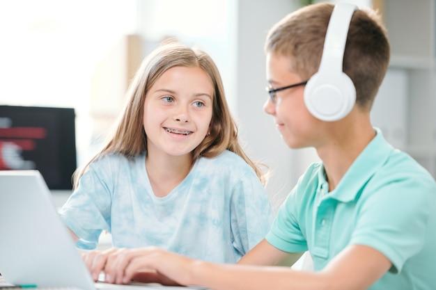 Zwei freundliche klassenkameraden der mittelschule sitzen im klassenzimmer und besprechen daten für das seminar oder die nächste lektion
