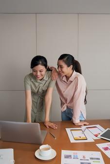 Zwei freundliche weibliche kollegen, die am schreibtisch bei der arbeit stehen und laptopschirm betrachten