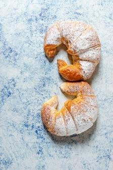 Zwei frisch gebackene croissants mit puderzucker auf blauem hintergrund mit textur