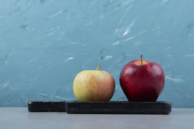 Zwei frische äpfel auf schwarzem schneidebrett.
