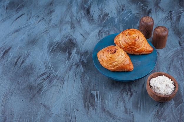 Zwei frische backwaren gefüllt mit fleisch und sauerrahm auf blauem brett.