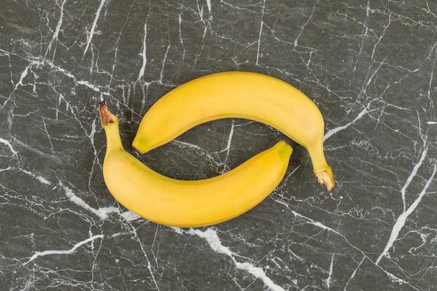 Zwei frische bio-bananen auf schwarzem stein