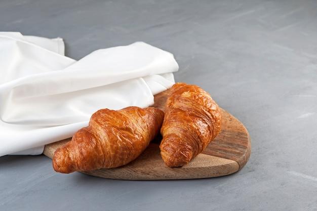 Zwei frische croissants liegen auf einem holzschneidebrett neben einer weißen serviette.