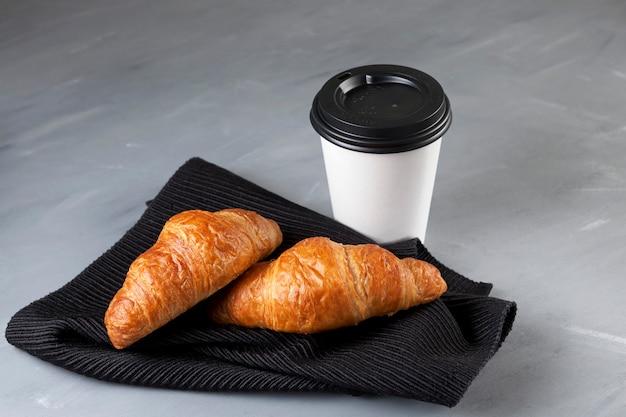 Zwei frische croissants liegen auf einer dunklen serviette. in der nähe steht eine weiße pappbecher mit kaffee. speicherplatz kopieren.
