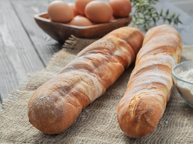 Zwei frische französische baguettes aus weißmehl neben hühnereiern und mehl